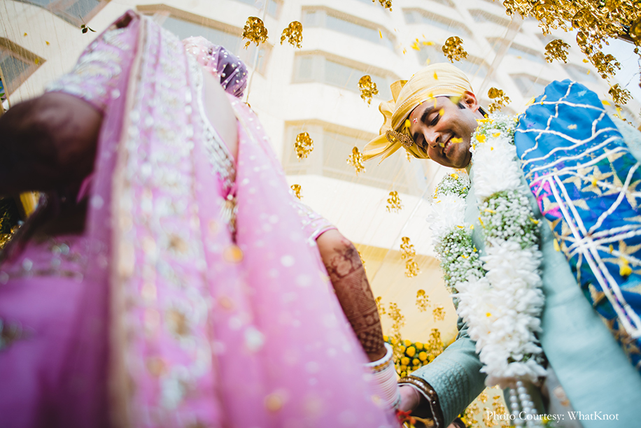 Bride wearing onion pink lehenga by Neeta Lulla with gold motifs, pearls, and sequins work, and the groom donned a soft pearl-blue sherwani