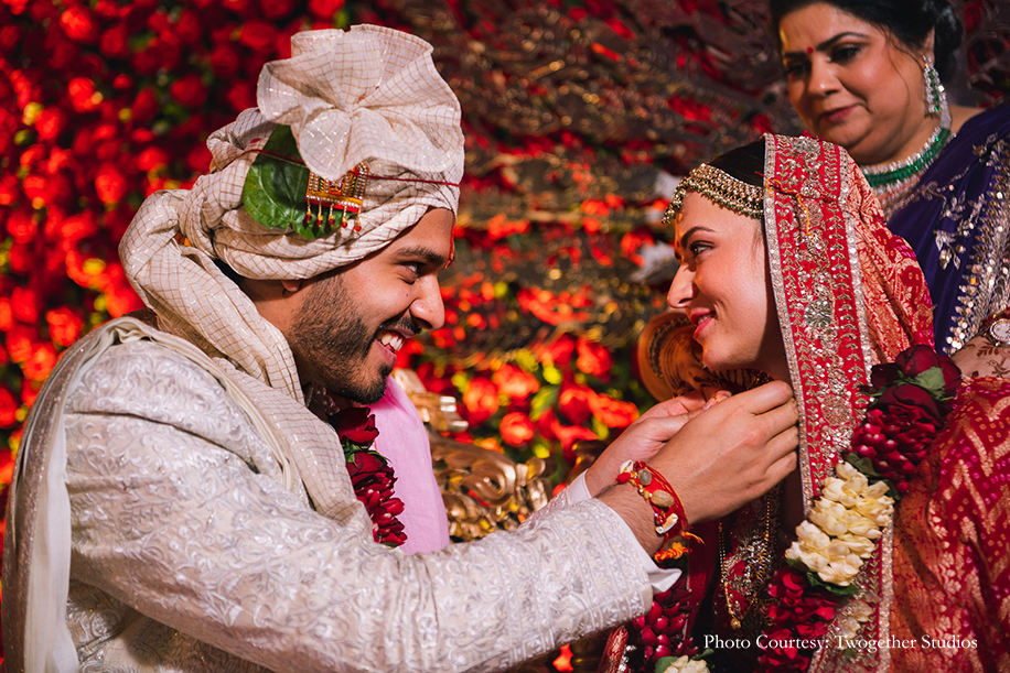 Bride wearing red and gold embroidered lehenga, statement nath and maang tikka for her wedding and Groom wearing white bandhgala fro the wedding at The Leela Ambience, Gurugram