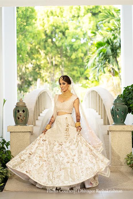 Bride wearing Blush lehenga with golden jewelry