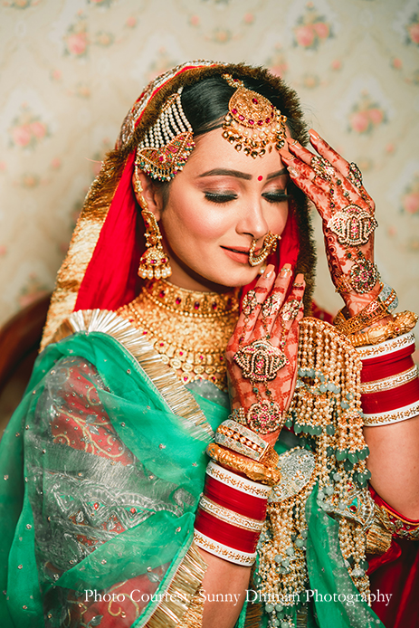 Bride wearing Rajasthani embroidery red and turquoise lehenga with statement jewelry