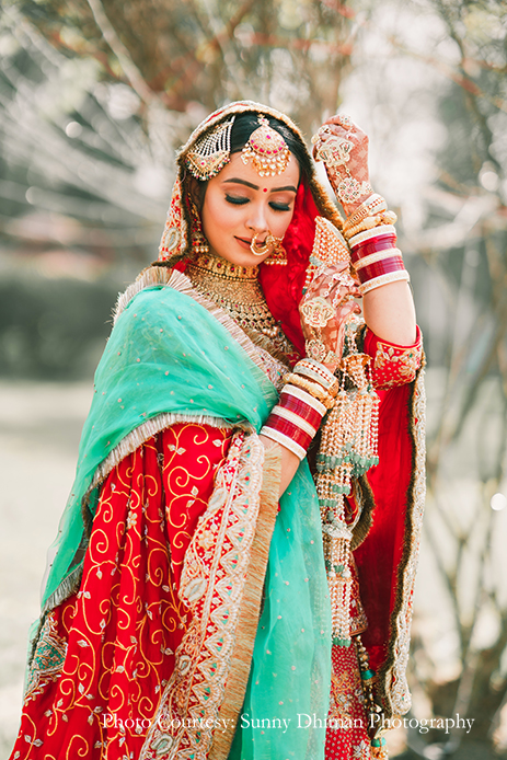 Bride wearing Rajasthani embroidery red and turquoise lehenga at Ludhiana