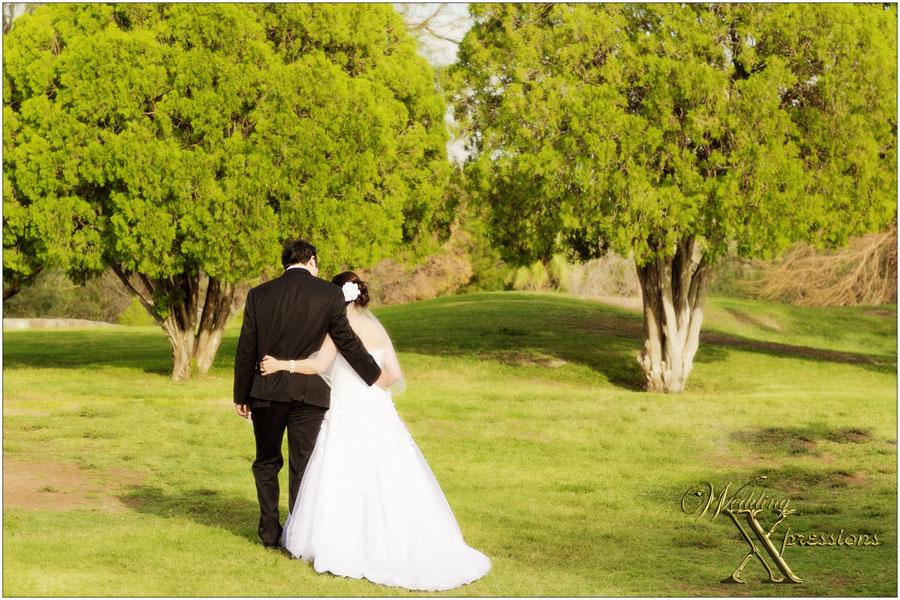 bride and groom walking away in park