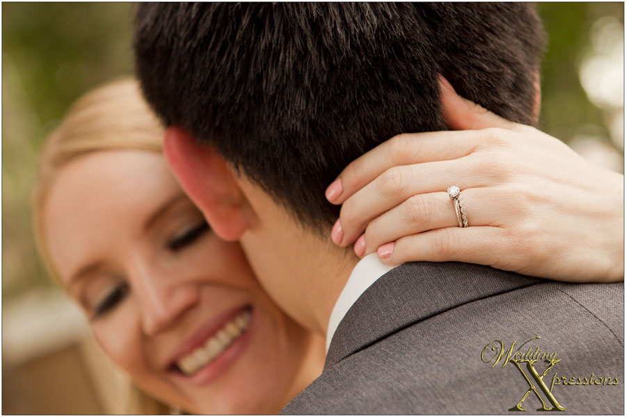 bride's ring while embracing groom