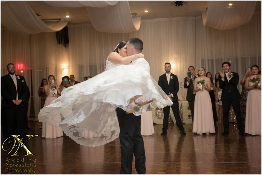 groom carries bride during wedding at Grace Gardens