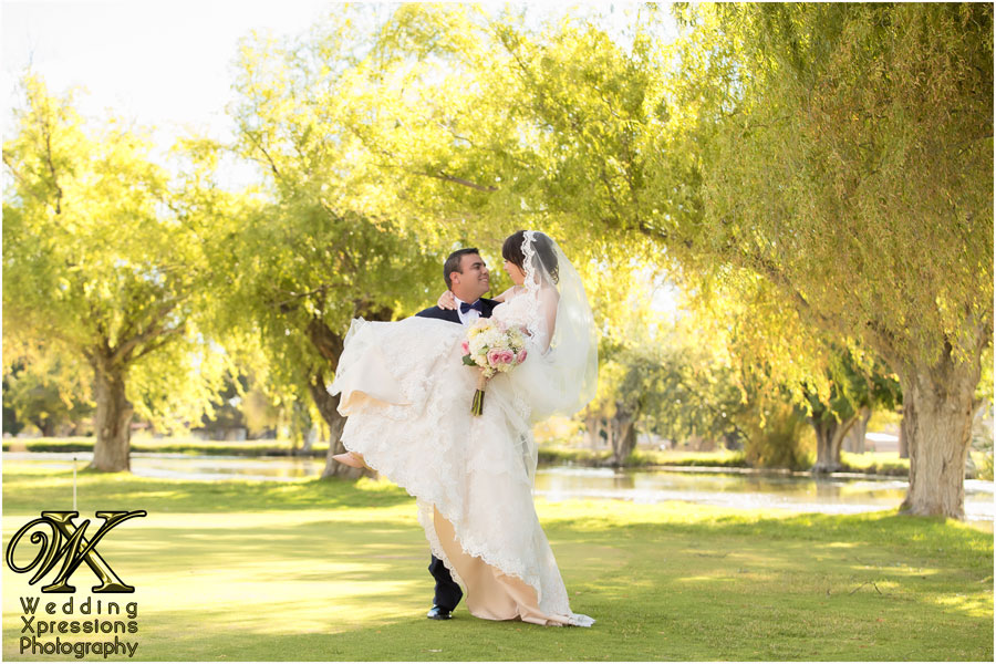 groom carrying bride near lake in El Paso Texas