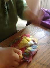 Child playing with multicoloured playdough made by an easy homemade recipe