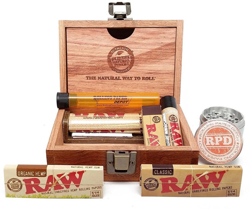 A bundle of weed gadgets including a beautiful Wooden Box from RAW, Rolling Papers, a Roller, Tips and RPD Grinder and Doobtube