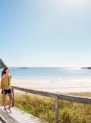 Couple walking on the beach on a weekend getaway NZ