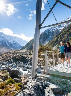 Couple walking over a bridge at Hooker Valley Track Mt Cook Aoraki National Park