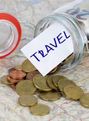 Jar of coins and bills and with a note saying Travel topped over and spilled over a map
