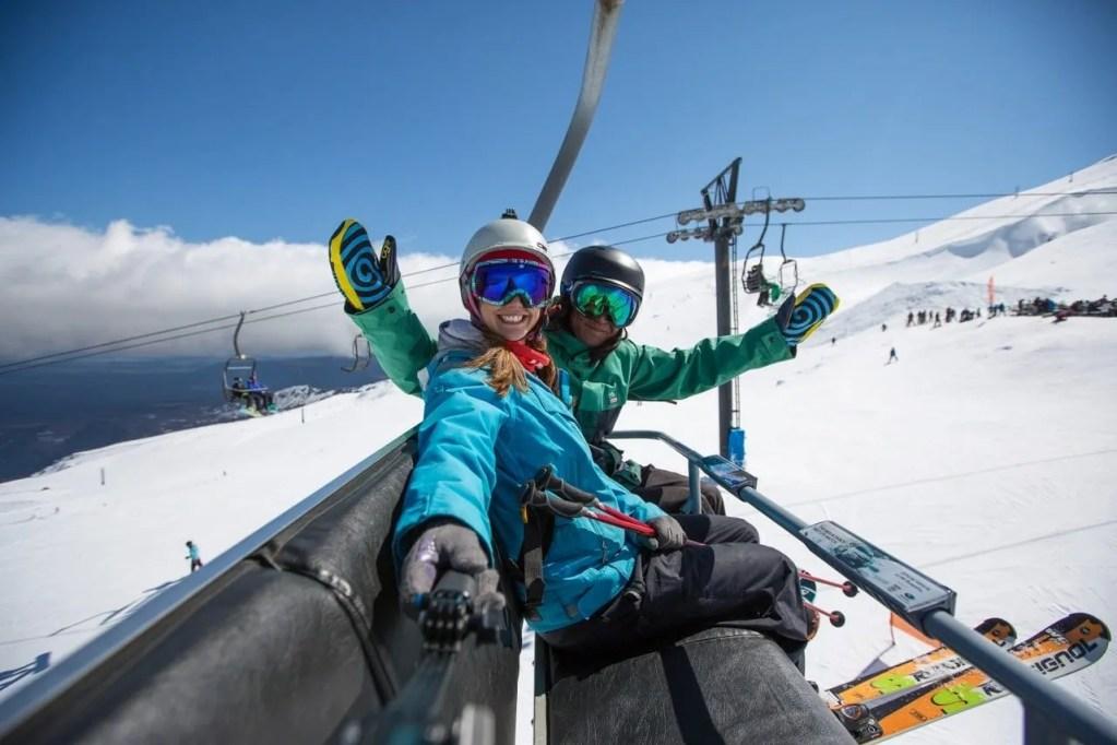 tow people in ski gear taking a fun selfie on the chair lift at turoa ski field on mt ruapehu