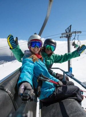 tow people in ski gear taking a fun selfie on the chair lift at turoa ski field on mt ruapehu