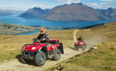 Two quad bikers with red quad bikes ride a dirt road on Queenstown Hills and Lake Wakatipu