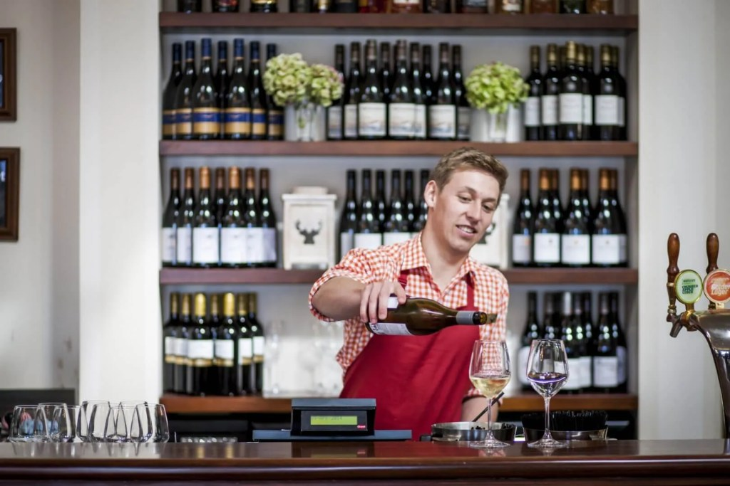 bartender at walter peak high country farm pouring a glass of red wine