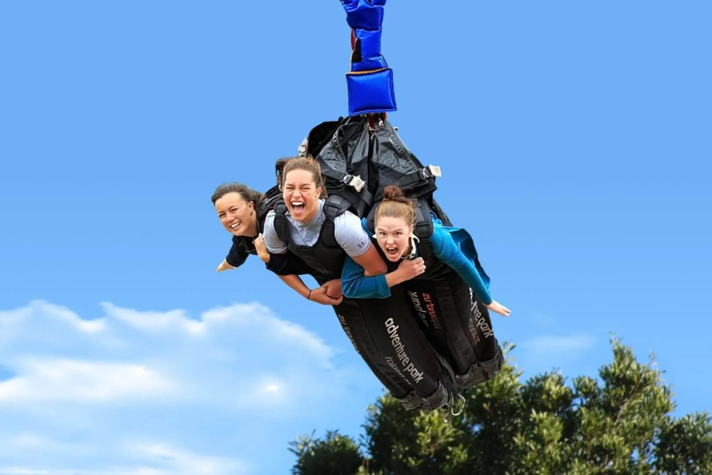 Three girls in body bags on the Swoop Swing in Velocity Valley Rotorua New Zealand