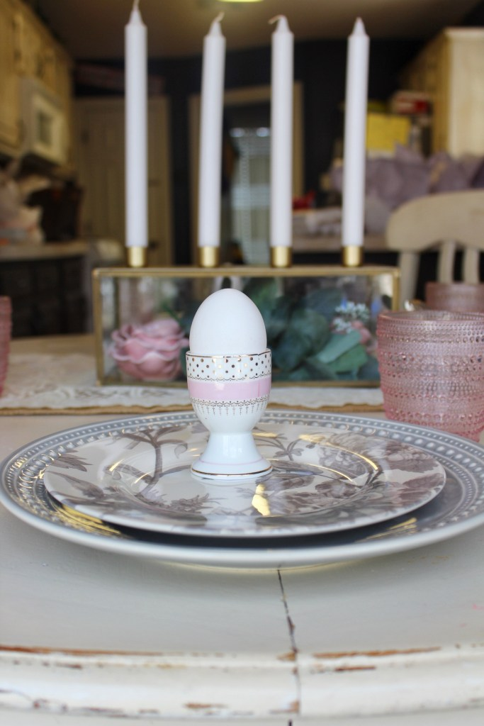 pink and gold egg cups for Easter eggs with gray plates.