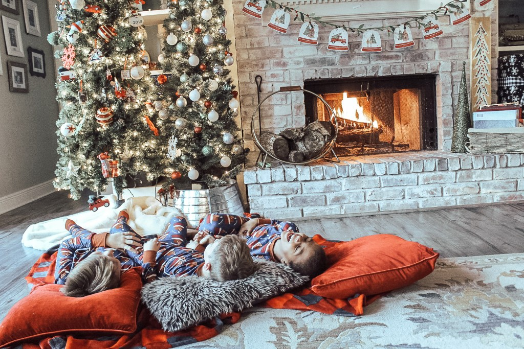 Boys laughing in front of fireplace ready to watch holiday movies