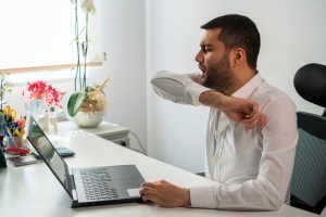 man coughing into his elbow with laptop on desk