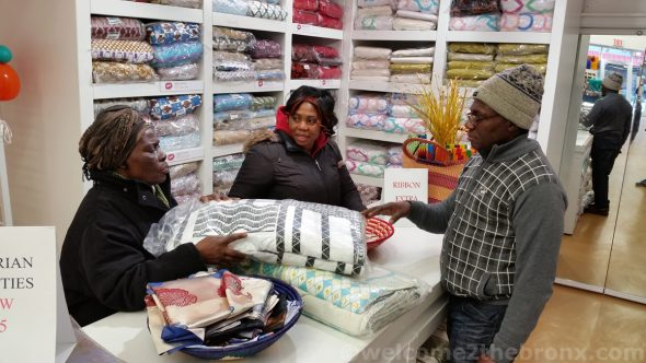 Osei Bonsu, Holland Textiles' Business Developer, goes over some fabrics with fellow Ghanaian customers.