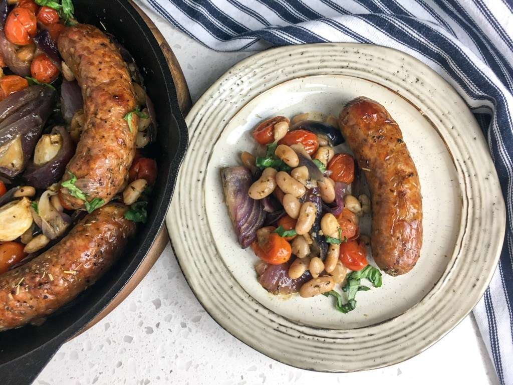 Roasted Italian Sausages with  tomatoes and white beans on a plate.