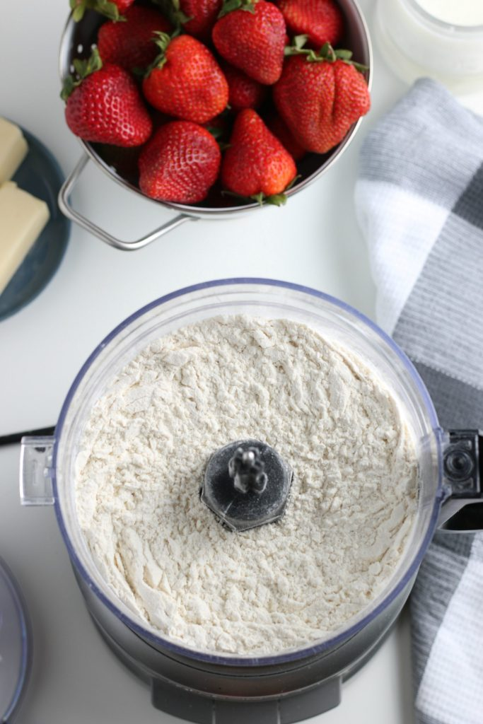 Strawberries in a bowl and flour in a food processor