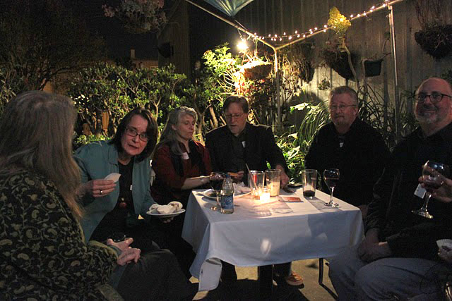 A gaggle of WELL members gather at a patio table.