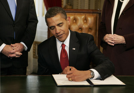 U.S. President Barack Obama signs his first act as president, a proclamation, after being sworn in as the 44th President of the United States during the inauguration ceremony in Washington January 20, 2009. REUTERS/Molly Riley (UNITED STATES)