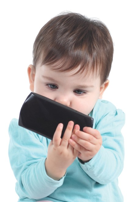 Casual baby watching attentive a mobile phone