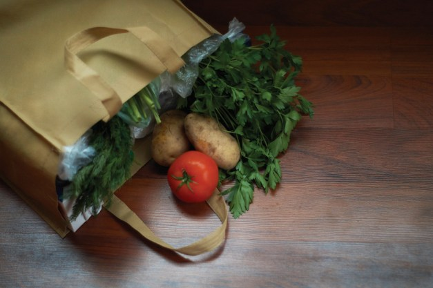 groceries and fresh produce in bag on wood floor