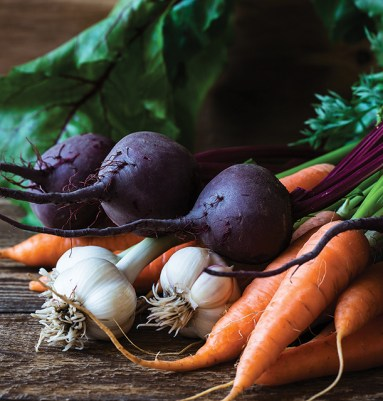 Bunch of fresh organic beetroots, garlic and carrots on wooden rustic table