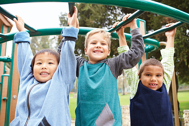 Three Young Boys On Climbing Frame In Playground