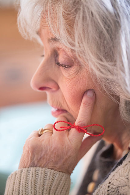 Close Up Of Senior Woman With String Tied Around Finger As Reminder