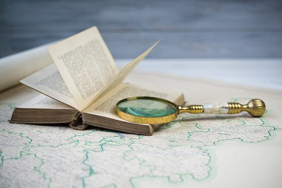 Old beautiful golden magnify glass on ancient book and old map