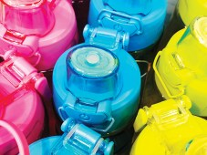 A set of safe reusable bottles with water from stainless steel in pink, yellow and blue.