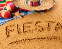 The word Fiesta written on a sandy beach, with sombrero, traditional serape blanket, starfish and maracas (studio shot - warm color and directional light are intentional).