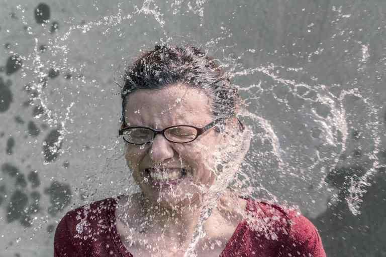 Frau spritzt Wasser ins Gesicht
