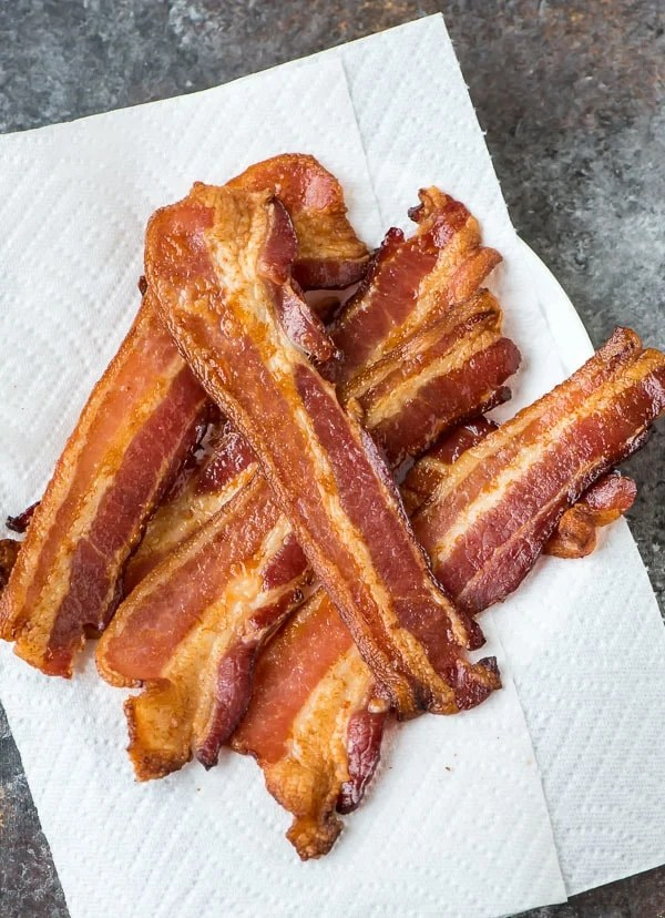 Crispy strips of oven baked bacon on paper towels