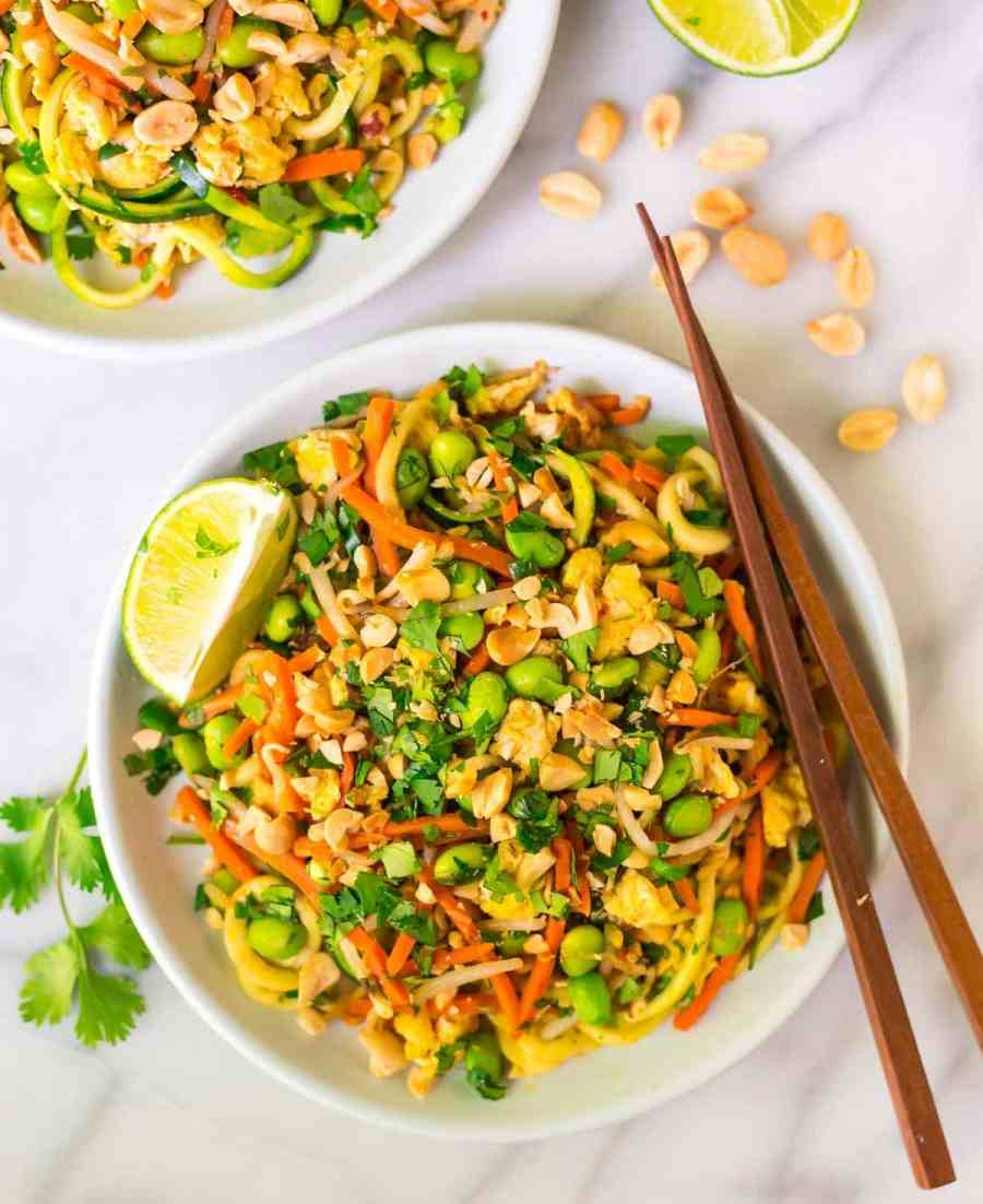 Easy Vegetarian Pad Thai with Zucchini Noodles in a white bowl with chopsticks and garnished with lime wedges, cilantro and peanuts