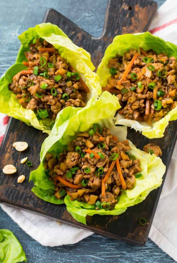 Three healthy Asian lettuce wraps on a serving board
