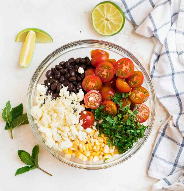 Vegetables, cheese, herbs, and beans in a bowl