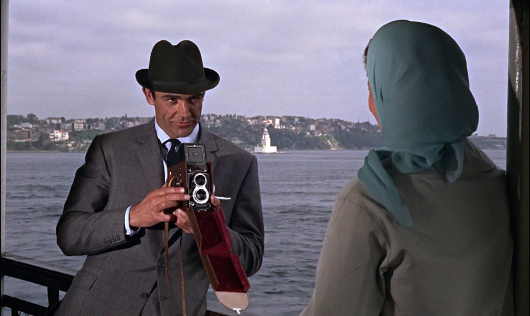 Sean Connery is taking photos of Daniela Bianchi on the Istanbul ferry on the Bosporus and iconic Maiden's Tower in the background on the Bosporus.