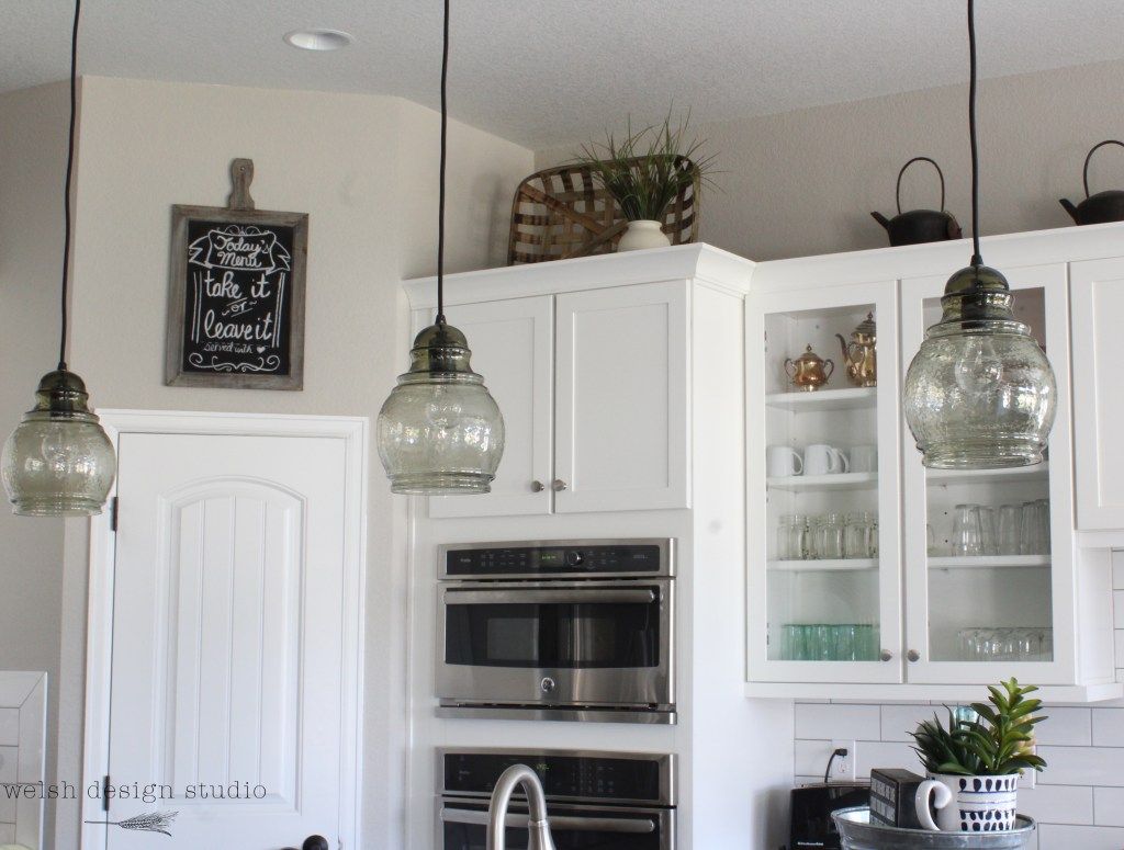 white kitchen with glass pendant lights
