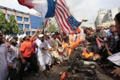 Bangladeshi Muslims burn U.S. and French flags as they shout slogans during a pr