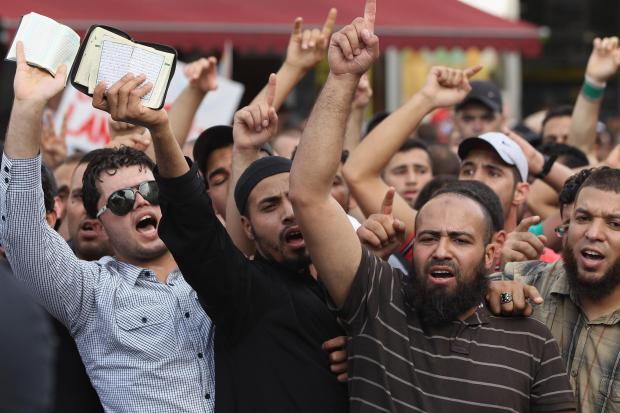 """<br /><br /><br /> Muslime protestieren Mitte August 2012 gegen die rechtspopulistische Splitterpartei """"Pro Deutschland"""" in Berlin. In den Händen halten sie Exemplare des Koran<br /><br /><br />"""