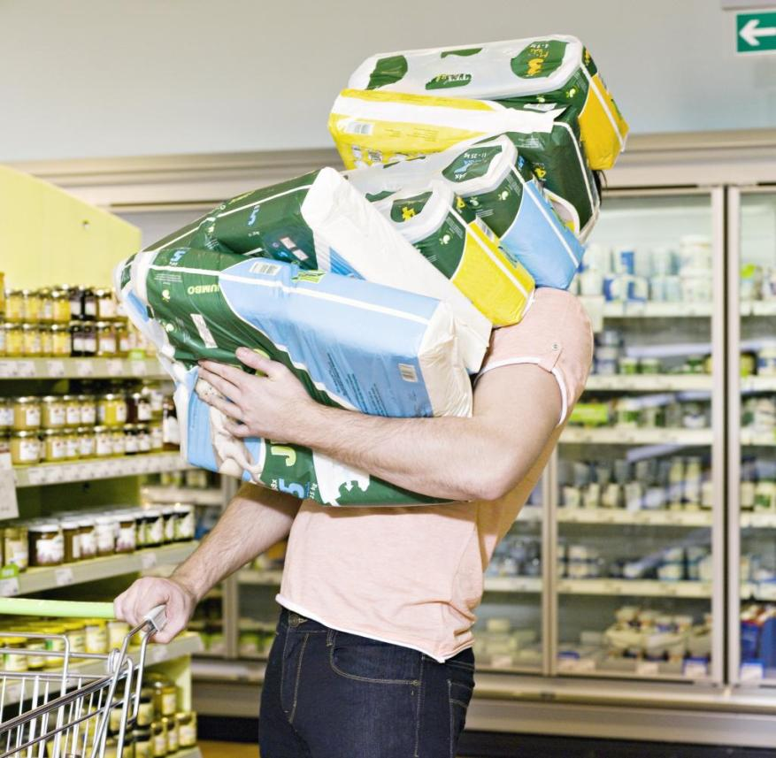 man carrying chemist`s produce in supermarket