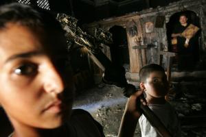 Palästinensische Kinder mit einem verkohlten Kruzifix in einer ausgebrannten Kirche. Aufgebrachte Muslime hatten sie nach islamkritischen Äußerungen des Papstes im Jahr 2006 angezündet