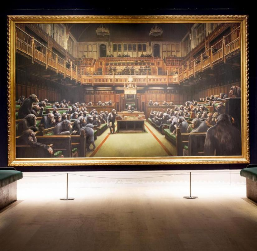 03 October 2019: Moments ago in London, Banksyís derisive portrayal of The House of Commons reduced to an assembly of parliamentary primates achieved a record £ 9,879,500 / $ 12,142,893 / Ä11,127,304 in Sothebyís Contemporary Art Evening Auction (est. £ 1.5-2 million) . The hammer came down after thirteen minutes of competitive bidding, with ten determined collectors driving the price well beyond the previous record of $ 1.8m. Spanning an impressive thirteen feet, this is the largest known canvas by the anonymous street artist whose subversive practice has granted him a reputation of infamy as much as world renown. Banksy first unveiled the painting, then titled Question Time, a decade ago as part of his ground-breaking Banksy vs. Bristol Museum exhibition, which famously drew over 300,000 visitors to become one of the worldís top ten most-visited shows of 2019. The painting has since been reworked by the artist and more recently retitled. Once glowing, the Commonsí lamps have been snuffed-out by Banksy, while the upturned banana of an ape in the foreground now faces downwards; in addition to these and other subtle adjustments, the painting was also given a new name: Devolved Parliament. [ Rechtehinweis: picture alliance / Photoshot ]