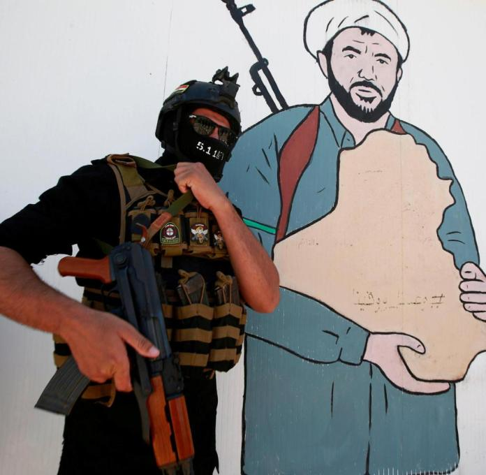 A PMF fighter poses in front of a mural in the Iraqi city of Najaf