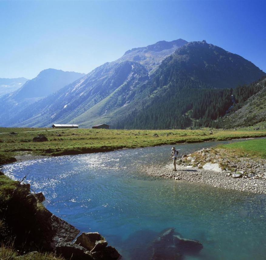 A fisherman stands on the Krimmler Ache in the Hohe Tauern National Park