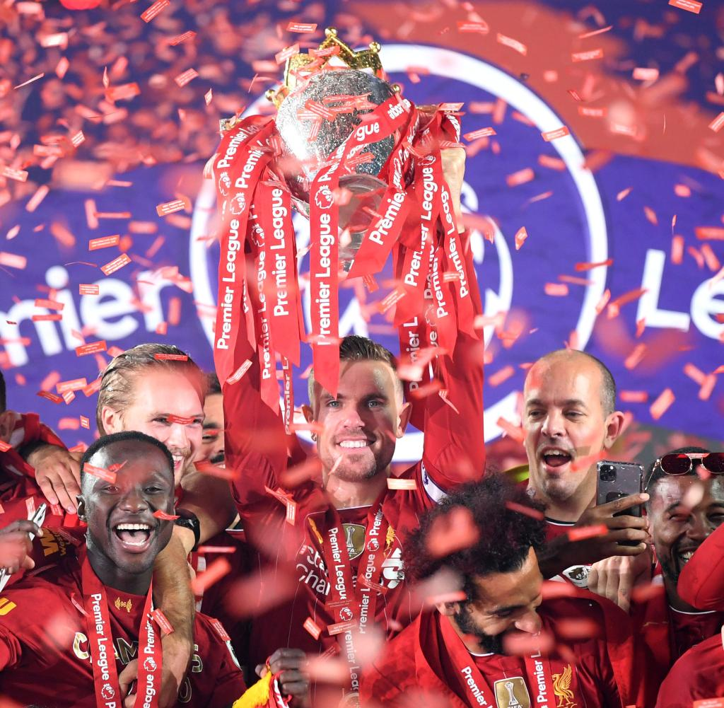 Historic moment: The Liverpool players hold the trophy in their hands